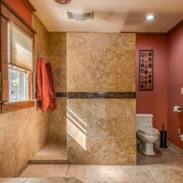 This project has a mud-set shower base with a curb in a staggered tile pattern. The Braun exhaust fan also provides heat. Floor tile is 18x18.