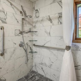 This project features 12x24 marble tiles on floor and wall.  A barrier-free shower with a trench drain. The shower has an L-shaped curtain for water containment. The shower head is handheld and  sits on a grab bar for height adjustment as needed.  Grab bars for accessibility. Corner shelves are adjustable.